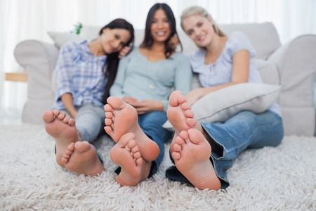 Friends relaxing on floor and smiling at the camera at home in living room