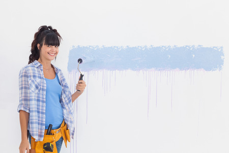 Woman painting wall blue and smiling at camera at home in empty room photo