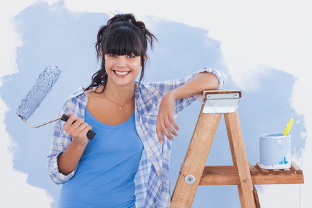 home improvement: Woman holding paint roller leaning on ladder smiling at camera Stock Photo