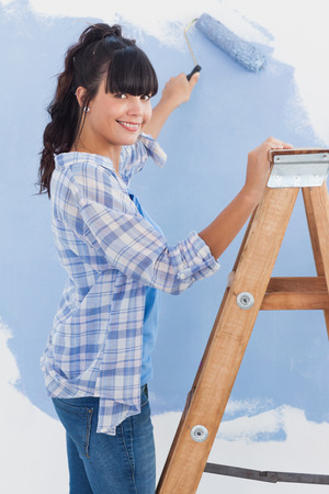 Woman using paint roller smiling at camera painting wall in blue photo