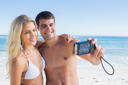 Man taking self portrait of him and pretty girlfriend at the beach photo