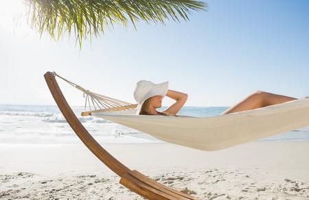 unwind: Woman wearing sunhat and bikini relaxing on hammock at the beach