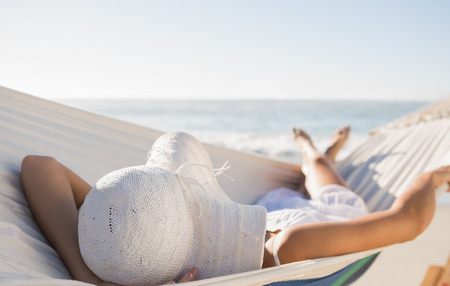 escapism: Peaceful woman in sunhat relaxing on hammock at the beach