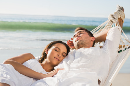 Peaceful couple napping in a hammock at the beach photo