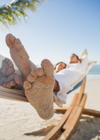 Close up of sandy feet of couple sleeping in a hammock on the beach photo