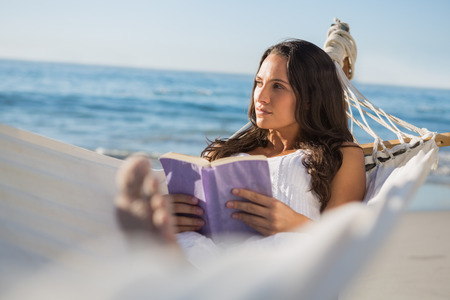 Woman lying on hammock holding book and thinking on the beach photo