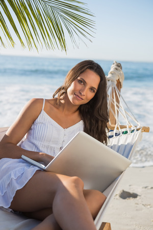 Brunette sitting on hammock with laptop smiling at camera on the beach photo