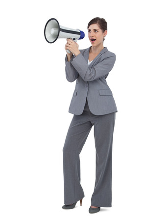 Businesswoman with loudspeaker on white background photo