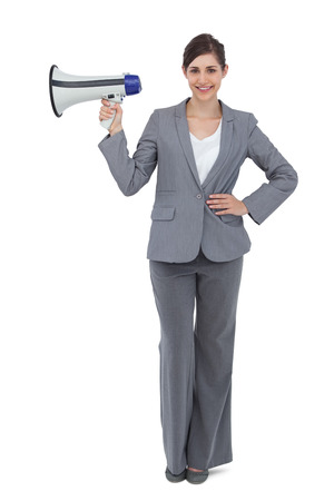 Smiling businesswoman on white background holding loudspeaker photo
