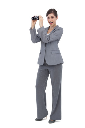 Astonished businesswoman on white background posing with binoculars photo