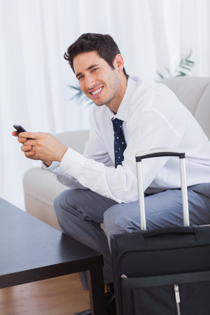 Happy businessman with suitcase and mobile phone sitting on couch  photo