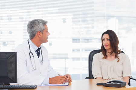 Doctor talking with his patient and writing on notebook in medical office photo
