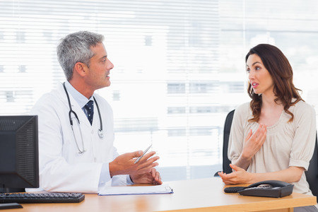 Patient talking with her doctor about illness in medical office photo