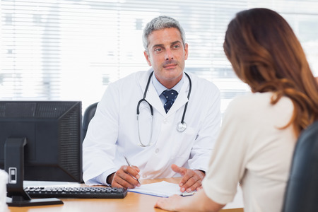 Doctor listening to his patient talking about her illness in medical office photo