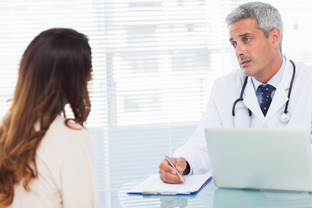 Serious doctor talking with his patient and writing on a notebook in medical office photo