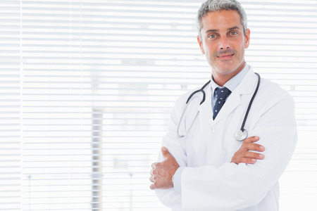 Smiling doctor crossing his arms in medical office photo