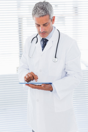 Doctor using tablet pc in medical office photo