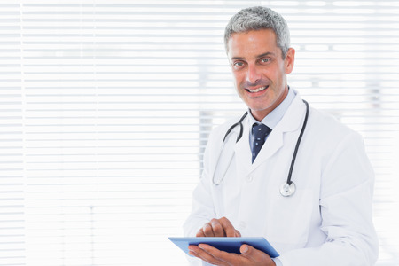 Smiling doctor using tablet pc in medical office photo