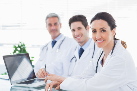 Doctors with laptop smiling at camera in medical office