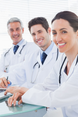 Smiling doctors looking at camera in medical office photo