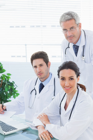 Team of doctors working together looking at camera in medical office photo