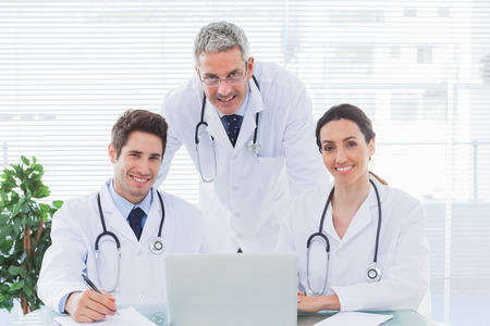Team of doctors working together with their laptop looking at camera in medical office photo