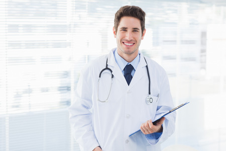 Smiling doctor holding files and looking at camera in medical office photo