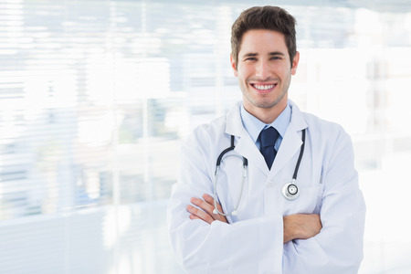 Smiling doctor crossed his arms and looking at camera in medical office photo