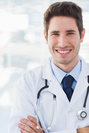 Happy doctor crossed his arms looking at camera in medical office photo