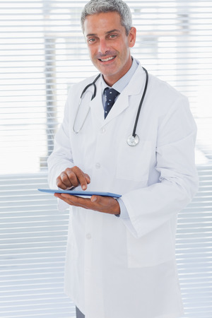 Smiling doctor holding his tablet pc and looking at camera in medical office photo