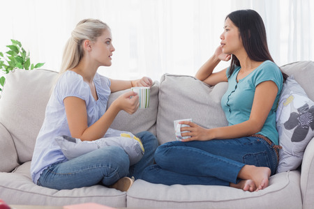 conversation: Friends drinking coffee and having a serious chat at home on the couch Stock Photo