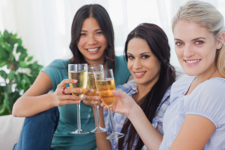Cheerful friends enjoying white wine together smiling at camera at home on couch photo