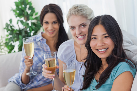 Happy friends enjoying champagne together looking at camera at home on couch photo