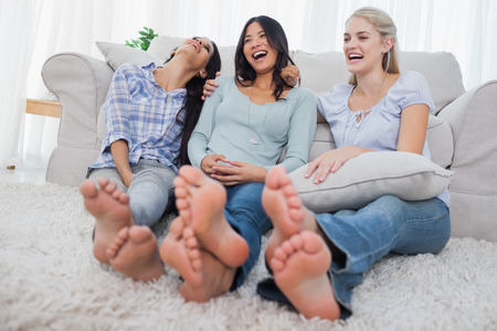 Friends relaxing on floor and laughing at home on couch photo