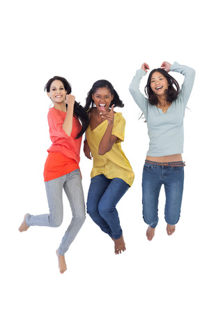 salto largo: Mujeres j�venes Diversos saltando y mirando a la c�mara sobre fondo blanco