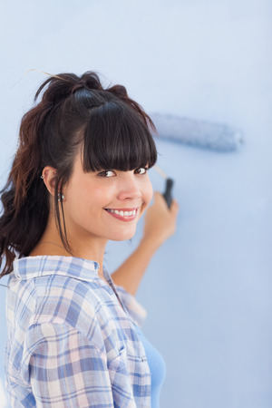 Cute woman painting wall blue and smiling at camera in new home photo