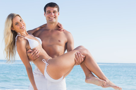 Man carrying his pretty girlfriend smiling at camera at the beach photo