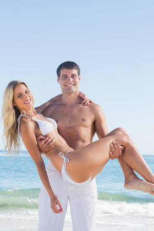 Strong man carrying his pretty girlfriend smiling at camera at the beach photo