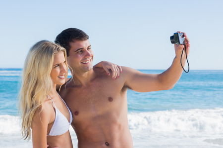 Man taking self portrait of him and girlfriend at the beach photo