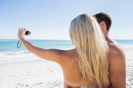 Blonde taking picture of herself with boyfriend at the beach photo