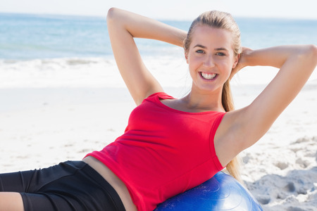 sit ups: Fit blonde doing sit ups on exercise ball on the beach