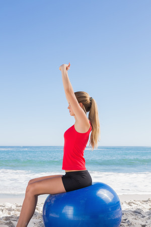 ball stretching: Fit woman sitting on exercise ball stretching arms on the beach Stock Photo