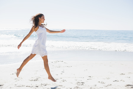 woman beach dress: Happy brunette in white sun dress skipping on the sand on the beach Stock Photo