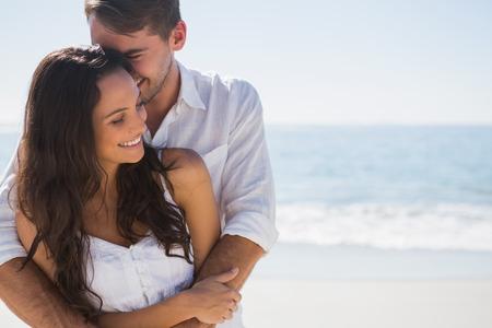 Atractiva pareja abrazos en la playa