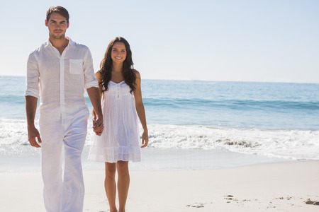 Beautiful couple holding hands and walking towards camera at the beach photo