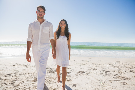 man long hair: Beautiful couple holding hands and walking towards camera at the beach