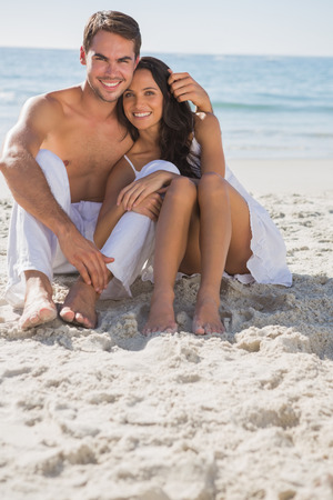 glamour couple: Embracing couple smiling at camera sitting on sand at the beach