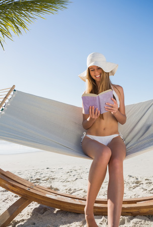 Happy blonde wearing sunhat sitting on hammock reading book at the beach photo