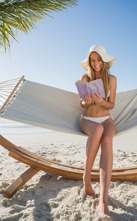 Cheerful blonde sitting on hammock reading book at the beach photo