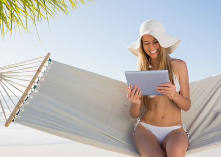 escapism: Cheerful blonde sitting on hammock using tablet pc at the beach Stock Photo